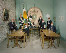 Inszeniertes Gruppenbild der Studentenverbindung 'Akademische Verbindung Froburger'. Alle stehen oder sitzen in Ihren Uniformen um einen Tisch.