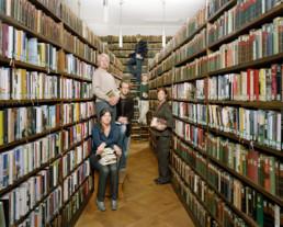 Inszeniertes Gruppenbild von Mitglieder einer Lesegesellschaft. Die Männer und Frauen stehen zwischen den Bücherregalen.