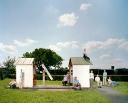 Inszeniertes Gruppenbild von Mitgliedern eines Astronomischen Vereins. Die Leute stehen und sitzen um und auf einem kleinen Haus für ein astronomisches Fernrohr