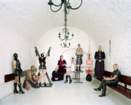 Inszeniertes Gruppenbild von Mitglieder von einem BDSM Stammtisch. Die Männer und Frauen sind in ihren Fetisch Kleider in einem hellen Kellergewölbe.