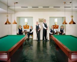 Inszeniertes Gruppenbild von Mitgliedern von einem Billard-Club. Die Männer stehen mit Ihren Queues um zwei Billardtische.