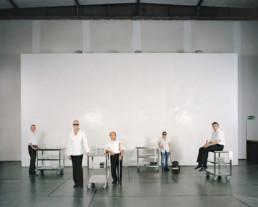 Inszeniertes Gruppenbild von Menschen mit einer Sehbehinderung, welche in einem Restaurant für blinde Personen arbeiten. Der Gastronomie Raum ist für die sehenden Besucher ganz dunkel - ein dunkel Restaurant. Die Leute stehen alle in Ihrer Service Kleidung vor einer hellen Wa