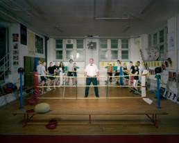 Inszeniertes Gruppenbild von Mitglieder von einem Boxclub in einem Boxkeller. Der Ringrichter steht alleine im Ring, die Boxer stehen um den Ring.