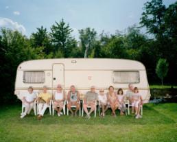Inszeniertes Gruppenbild von Mitglieder von einem Camping- und Caravaning-Club auf einem Campingplatz. Diese Mitglieder sitzen vor einem Wohnwagen auf Klappstühlen.