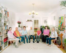 Inszeniertes Gruppenbild von Mitglieder eines Zirkels im Bereich spirituelle Mentalität. Die Männer und Frauen sitzen in einem Halbkreis in einem Zimmer.