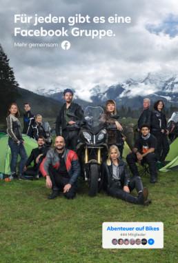 In einer Berglandschaft sind auf einer Hochebene Zelte aufgeschlagen. Davor Motorradfahrer mit und auf ihren Motorräder.