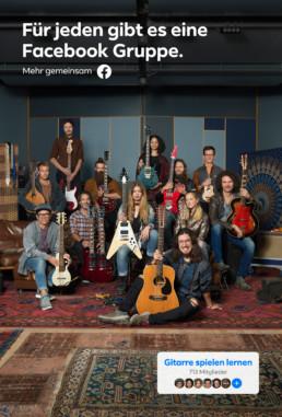 In einem Musikraum mit Sofas, Sessel und Hocker sitzen und stehen viele verschiedene Menschen mit ihren Gitarren.