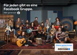 In einem Musikraum sitzen und stehen viele Menschen mit Ihren unterschiedlichsten Gitarren auf Sofas, Hocker oder Sessel.