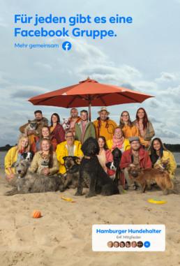 Am Sandstrand von einem grossen Fluss stehen und sitzen Hundehalter mit ihren Hunden in Regenbekleidung unter grossen Sonnenschirmen beisammen.
