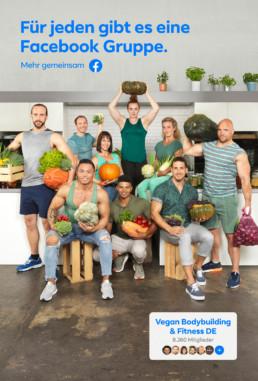 In einer hellen, modernen Küche stehen Bodybuilder und Bodybuilderinnen umgeben von Früchten und Gemüsen in ihrer Bodybuildingbekleidung zusammen und posieren zur Kamera.