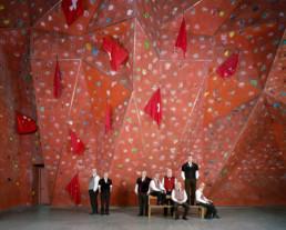 Inszeniertes Gruppenbild von Mitglieder von einem Fahnenschwingerverein. Die Männer sitzen und stehen in einer Kletterkalle.