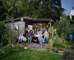 Inszeniertes Gruppenbild von Mitglieder von einem Familiengärtnerverein. Die Leute sitzen beisammen in einem Gartenhaus.