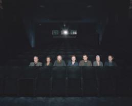 Inszeniertes Gruppenbild von Mitglieder von einem Filmclub. Diese sitzen alle in einer Reihe in einem Kinosaal.