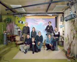 Inszeniertes Gruppenbild von Mitglieder von einem Fotoclub. Diese sitzen und stehen mit ihren Kameras vor einem bemalten Hintergrund in einem Fotostudio.