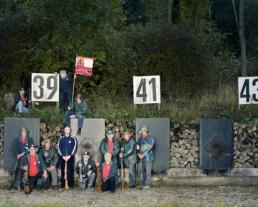 Inszeniertes Gruppenbild von Mitglieder von einem Schützenverein. Die Männer stehen mit ihren Gewehren vor dem Kugelfang.