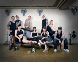 Inszeniertes Gruppenbild von tätowierten Leuten. Die Männer und Frauen stehen und sitzen um und auf einer Chaiselongue