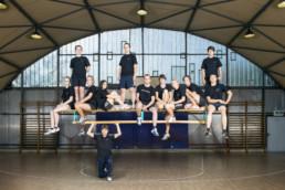 In einer Turnhalle, ist ein Sportlehrer zu sehen, er hält einen Schwedenbalken (digitale Bildbearbeitung) auf welchem all seine Schüler sitzen und stehen.