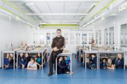 In einem Klassenzimmer sitz ein Biologie Lehrer auf dem Tisch und hält eine Gehirn aus Plastik zur Anschauung in der Hand. All seine Schüler verstecken sich unter den tischen und gucken hervor.