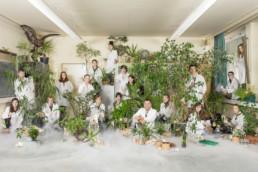 In einem Schulzimmer stehen viele Pflanzen und präparierte Tiere. Dazwischen raucht und qualmt es. Der Lehrer und seine Schüler und Schülerinnen sitzen und stehen zwischen den Pflanzen, am Boden und auf dem Kasten.