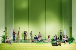 uf der Bühne einer Schulaula sitzen und stehen alle Schüler und Schülerinnen wie in einem modernen Bild Déjeuner nur l'Herbe herum. Mit Essen, Zeichen und Staffelei, Bücher, … Die Lehrerin sitzt entspannt auf einer Pic-Nic-Decke