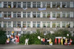 Vor einem Schulhaus und aus dessen Fenster schauen viele Schüler und Schülerinnen. Alle halten Plakate in der Hand mit Aufschriften wie ja, nein, dagegen, … Die Lehrerin steht mit einem Besen und einem Megafon in der Hand vor dem Schulhaus.