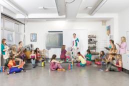 In einem Zeichnungssaal steht der Lehrer in weisser Kleidung vor einer weissen Wand. Alle Schülerinnen sitzen und stehen ringsum und zeichnen. Einige malen die Kleidung des Lehrers farbig an