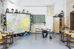 IN einem Klassenzimmer sitzt der Lehrer an seinem Lehrerpult und spielt mit Soldaten-Figuren. Alle Schüler und Schülerinnen verstecken sich: Hinter der Landkarte, auf und im Kasten,… .