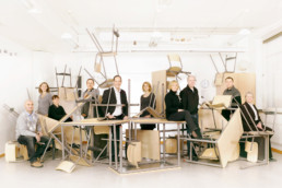 In einem Klassenzimmer ist ein grosser Haufen an Schulpulten, Schultischen und Stühlen. Dazwischen sitzen und stehen diverse Lehrpersonen.