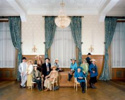 Inszeniertes Gruppenbild von Mitglieder von einem Hutclub. Die Damen und Herren sitzen und stehen chic gekleidet in einem edlen Ballsaal. Alle tragen einen Hut.