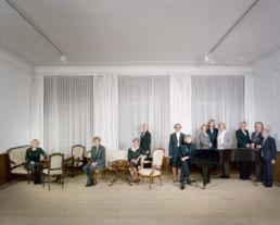 nszeniertes Gruppenbild von Mitglieder von einem wohltätigen Service-Club. Die Frauen sitzen und stehen alle um einen Klavierflügel in einem grossen Raum.