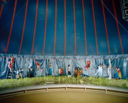 Inszeniertes Gruppenbild von Mitglieder von einem Jugendzirkus. Die Kinder und Jugendliche stehen im Zirkuszelt vor der Rundleinwand in Ihren Vorstellungskleidung und mit ihren artistischen Accessoires.