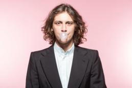 Ein junger Mann in einem dunklen Anzug macht eine Kaugummiblase. Er steht vor einem pinken Hintergrund.