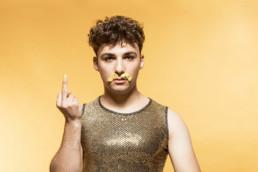 Ein junger Mann mit einem goldenen Muskle-Shirt zeigt uns den Stinkefinger. Er hat sich mit Senf einen Schnauz gemalt. Der Hintergrund ist gelb.