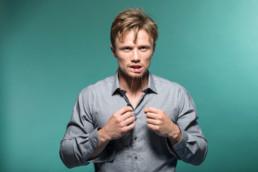 Ein junger Mann pflegt sich seine Zähe mit einer Zahnseide. Er trägt ein blaues Hemd und steht vor einem petrolfarbenen Hintergrund.