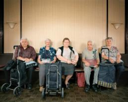 nszeniertes Gruppenbild von Kaffeerahm-Deckels Sammler und Sammlerinnen. Die Männer und Freuen sitzen mit ihren Einkaufswagen in einem Raum auf einer Bank.