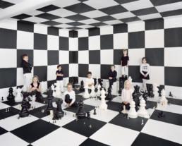 Inszeniertes Gruppenbild von Kinder in einem Raum mit Schachfiguren und Schachfeldern.