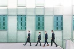 Vor einem Bürogebäude gehen vier gut gekleidete junge Herren im Anzug hintereinander her. In der Hand halten sie vor sich jeweils eine Banane.