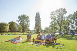 Auf einer Wiese im urbanen Umfeld sitzen in einem Schlauchboot junge Männer und trinken Bier. Um sie herum sind viele leergetrunkene Bierdosen.