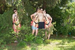 in einem Garten stehen junge Männer mit Küchenschürzen im Gebüsch. Aufgedruckt ist jeweils der leicht bekleidete Ausschnitt einer Frau.