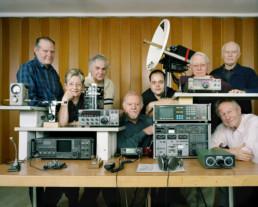 Inszeniertes Gruppenbild von Mitglieder von einem Kurzwellenamateur-Club. Die Männer und Frauen sind mit vielen Geräten abgebildet.
