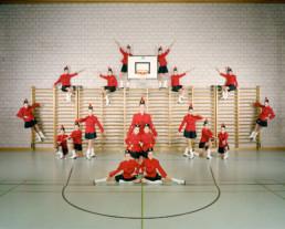 Inszeniertes Gruppenbild von Mitglieder einer Showtanzgruppe, welche in ihrer Mjorettenuniform-Kleidung einer Turnhalle symmetrisch vor einer Sprossenwand angeordnet sind.