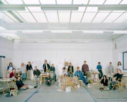 Inszeniertes Gruppenbild von Teilnehmer*innen einer Malklasse. Die Leute sitzen und sehen im grossen Zeichnungssaal hinter und neben Ihren Staffeleien.