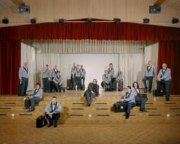Inszeniertes Gruppenbild von Mitglieder eines Musikvereins. Die Musiker und Musikerinnen sitzen und stehen in ihrer Auftrittsuniform auf einer Bühne in einem grossen Saal mit Ihren Instrumenten, welche alle in den Instrumenten-Koffern verräumt sind.