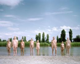 Inszeniertes Gruppenbild von Mitglieder der Interesse und Performancegruppe 'Naked Projects'. Die Männer und Frauen stehen alle nackt an einem Stadtsee