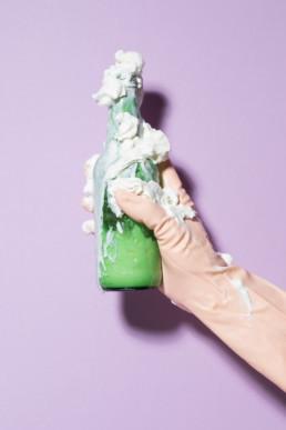 Eine Hand in einem hautfarbenen Plastikhandschuh hält vor einem lila Hintergrund eine Bierflasche, aus welcher viel Rasierschaum quillt