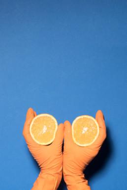 Zwei Hände in orangen Plastikhandschuhen halten je eine halbe Orange vor einem blauen Hintergrund