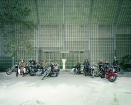 Inszeniertes Gruppenbild von Motorradfahrer und Motorradfahrerinnen auf ihren Motorräder in einem Industriegebiet.