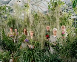 Inszeniertes Gruppenbild von Mitglieder*innen eines Orchideenclub. Alle stehen, dicht umgeben von vielen Orchideen und Pflanzen, in einem Gewächshaus.