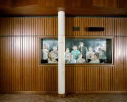 Inszeniertes Gruppenbild von Mitglieder eines Pfeifen-rauch- Vereins. Hinter Glas in einem abgetrennten kleinen Raum sitzen und stehen die Männer in ihrem Vereinshemden und rauchen Pfeife.