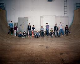 Inszeniertes Gruppenbild von Jugendlichen mit ihren Skateboards in einer Halfpipe.
